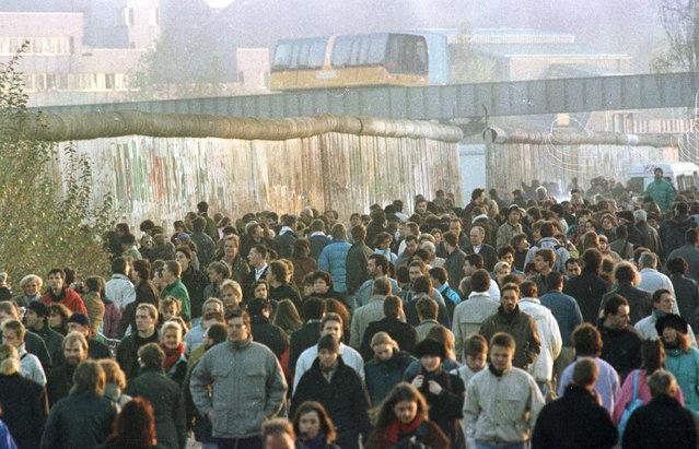 Thousands walk along the Berlin Wall between Potsdamer Platz and Brandenburg Gate November 18, 1989 file photo. (Photo by Reuters)
