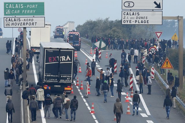 Dozens of migrants gather near lorries which head towards the ferry terminal in Calais, France, October 3, 2015. (Photo by Pascal Rossignol/Reuters)