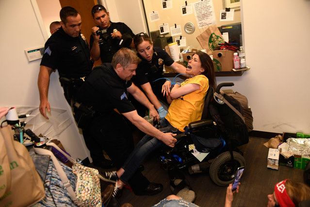 """Dawn Russell gets arrested by Denver police officers after refusing the vacate the offices of Senator Cory Gardner in Denver, Colorado on June 29, 2017. A handful of people, all of whom are with ADAPT, held a sit-in for 58 hours in the tiny front lobby space in the office of Colorado Senator Cory Gardner. They are asking the senator to vote against the new health care bill. As they were arrested protesters chanted """"I would rather go to jail than die without Medicaid"""". ADAPT is a national grass-roots community that organizes disability rights activists to engage in nonviolent direct action, including civil disobedience, to assure the civil and human rights of people with disabilities to live in freedom.  (Photo by Helen H. Richardson/The Denver Post via Getty Images)"""
