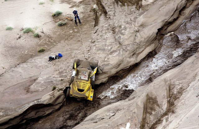 Pascal Larroque uses a cable to pull his car from the bank of a river during the 11th stage of the 2013 Dakar Rally from La Rioja to Fiambala, Argentina, January 16, 2013. (Photo by Bertrand Metayer/Le Parisien)