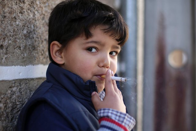 Fernando, 6-years-old, smokes a cigarette in the village of Vale de Salgueiro, northern Portugal, during the local Kings' Feast Saturday, January 5, 2018. (Photo by Armando Franca/AP Photo)