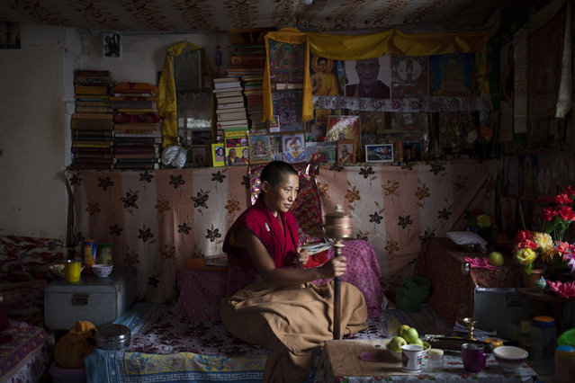 In this Saturday, September 27, 2014 photo, an Exile Tibetan nun Namdak Choeying, 44, prays in her room that she shares with two other nuns in Dharmsala, India. Back home in Tibet she aspired to be a fully ordained nun and escaped to India in 2006. Her five siblings and aged parents live in Tibet and she dreams about being reunited with them. Choeying said she immerses herself in prayers to keep her mind occupied. (Photo by Tsering Topgyal/AP Photo)