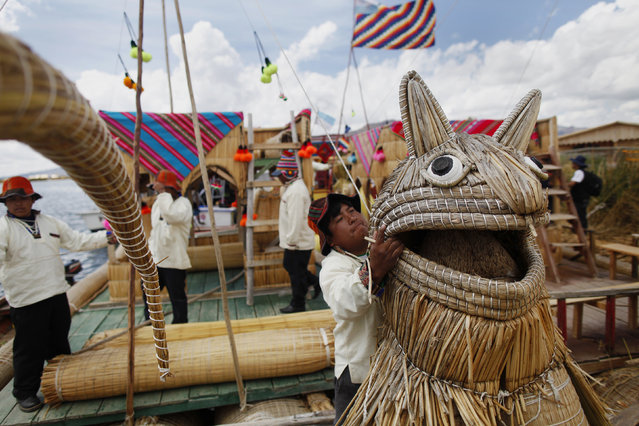 An Andean man prepares a totora raft at the shores of a Uros island at Lake Titicaca before a re-enactment of the legend of Manco Capac and Mama Ocllo in Puno November 5, 2014. (Photo by Enrique Castro-Mendivil/Reuters)