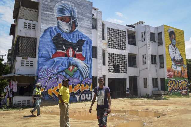 "Residents walk in front of informational murals painted on the side of an apartment block about the coronavirus and paying tribute to medical workers with the messages ""We'll Protect You"" and ""We Salute You"", in the Buxton residential estate of the coastal city of Mombasa, Kenya, Monday, August 17, 2020. (Photo by AP Photo/Stringer)"