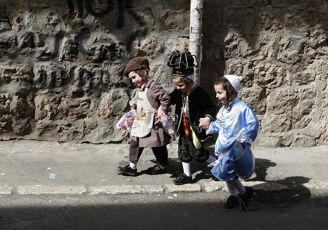 Boys wear costumes ahead of the Jewish holiday of Purim in Jerusalem's Mea Shearim neighbourhood February 20, 2013. Purim, which will be marked next week, is a celebration of the Jews' salvation from genocide in ancient Persia, as recounted in the Book of Esther. (Photo by Baz Ratner/Reuters)
