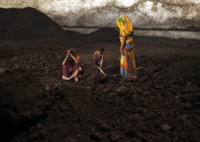 Labourers rest as a boy playfully shovels coal at a yard in the western Indian city of Ahmedabad November 20, 2014. India will allow locally registered foreign firms to mine and sell coal when commercial mining is permitted as part of the opening up of the nationalised industry after four decades, Coal Secretary Anil Swarup told Reuter. (Photo by Amit Dave/Reuters)