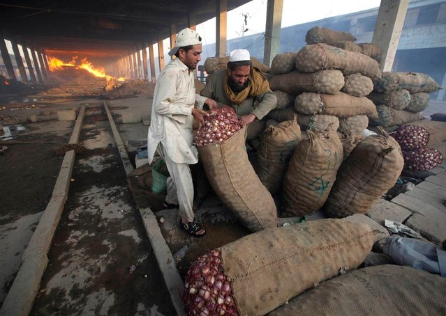 Men try to move sacks of onions to a safer place during a fire in a wholesale vegetable and fruit market on the outskirts of Karachi, Pakistan, on March 6, 2013. A fire broke out in the market Wednesday evening, causing massive damage. No casualties were reported. (Photo by Athar Hussain/Reuters)