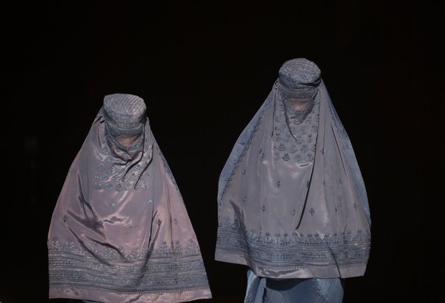 Afghan burqa-clad women walk as they leave a shop at a market in Mazar-i-Sharif, Afghanistan on December 12, 2017. (Photo by Farshad Usyan/AFP Photo)