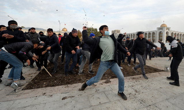 Supporters of nationalist Sadyr Japarov, who has styled himself as prime minister throw clumps of earth towards supporters of former Kyrgyzstan's President Almazbek Atambayev as they attend a rally in Bishkek on October 9, 2020. Two large crowds supporting rival politicians clashed in Kyrgyzstan's capital Bishkek as a power vacuum persisted and President Sooronbay Jeenbekov said he was ready to resign. (Photo by Vyacheslav Oseledko/AFP Photo)