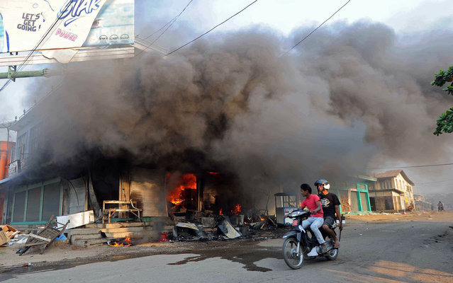 Residents ride a motorcycle past a burning building in riot-hit Meiktila, central Myanmar on March 22, 2013.  Charred bodies lay unclaimed on the streets of a riot-hit town in central Myanmar, witnesses said, as global pressure mounted for an end to the Buddhist-Muslim unrest. Parts of Meiktila have been reduced to ashes in the most serious communal violence to hit the former junta-ruled nation since last year, leaving the authorities struggling to bring the situation under control. (Photo by Soe Than Win/AFP Photo)