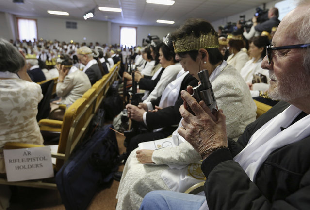 A man holds an unloaded weapon during services at the World Peace and Unification Sanctuary, Wednesday February 28, 2018 in Newfoundland, Pa. Worshippers clutching AR-15 rifles and other weapons participated in a commitment ceremony at the Pennsylvania-based church. The event Wednesday morning led a nearby school to cancel classes for the day. The church's leader, the Rev. Sean Moon, said in a prayer that God gave people the right to bear arms. (Photo by Jacqueline Larma/AP Photo)