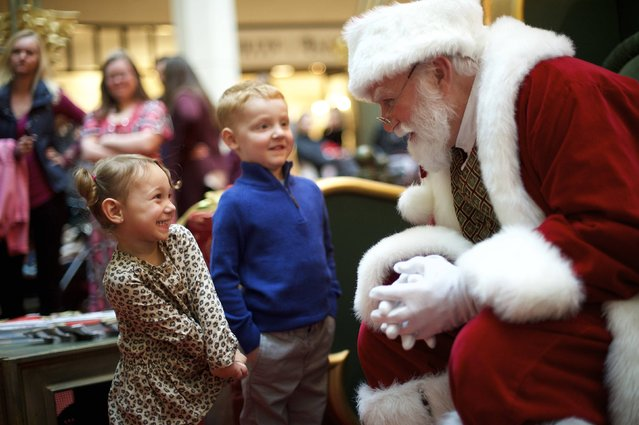 Brayden Knowles, 2, greets Santa Claus, with brother Brynlie, 4, at The Plaza, King of Prussia Mall, United State's largest retail shopping space, in King of Prussia, Pennsylvania on December 6, 2014. The 2.7 million square feet shopping destination is owned by Simon Property Group. Picture taken December 6, 2014. (Photo by Mark Makela/Reuters)