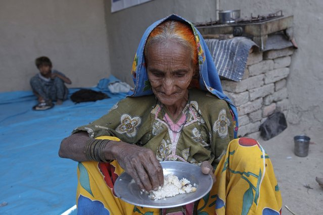Tulsi, a cotton picker eats her lunch of boiled rice while sitting in her home in Meeran Pur village, north of Karachi November 23, 2014. (Photo by Akhtar Soomro/Reuters)