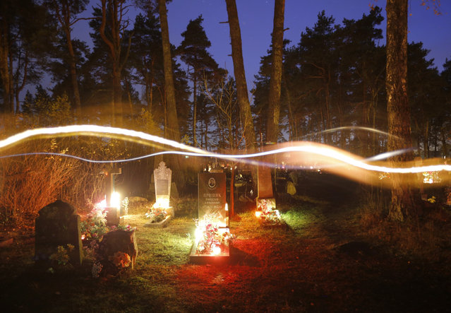 A long exposure photo showing people carrying candles to graves at a cemetery in the town of Rakov, some 45 kilometers (28 miles) northwest of Minsk, Belarus, Sunday, November 1, 2015. Belarusian Catholics marked All Saints Day by visiting graves of their relatives. (Photo by Sergei Grits/AP Photo)