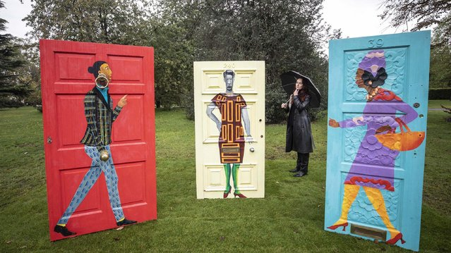 """A woman walks past Lubaina Himid's """"Five Conversations"""" which has been installed as part of the Frieze Sculpture 2020 exhibition at The English Gardens in Regent's Park, London on October 5, 2020, which features work from 12 leading international artists. (Photo by Richard Pohle/The Times)"""