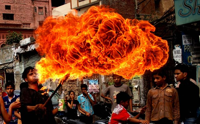 A boy blows fire during a religious procession in Amritsar, India, to celebrate the birthday of the Hindu god Rama, on April 19, 2013. (Photo by Sanjeev Syal/Associated Press)