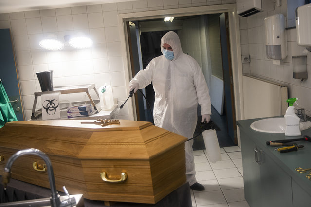 A worker, wearing a full protective equipment, disinfects the casket of someone who died of coronavirus COVID-19 at the Fontaine funeral home in Charleroi, Belgium, Tuesday, November 17, 2020. One of the hardest-hit countries in Europe, Belgium has reported more than 535,000 confirmed virus cases and more than 14,400 deaths linked to the coronavirus. (Photo by Francisco Seco/AP Photo)