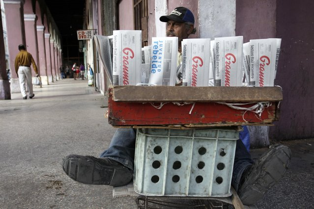 A Cuban man sits behind local newspapers for sale on a street in Havana December 17, 2014. (Photo by Reuters/Stringer)