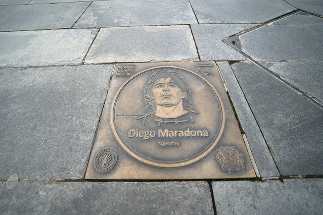 A plaque showing Argentina's Diego Maradona outside the National Football Museum in Manchester, England, Thursday November 26, 2020. Tens of thousands of fans were lining up to say goodbye to Diego Maradona on Thursday at the Argentine presidential mansion staging the funeral of one of football's greatest stars. Maradona died on Wednesday of a heart attack where he recovered from a brain operation on Nov. 3. (Photo by Jon Super/AP Photo)
