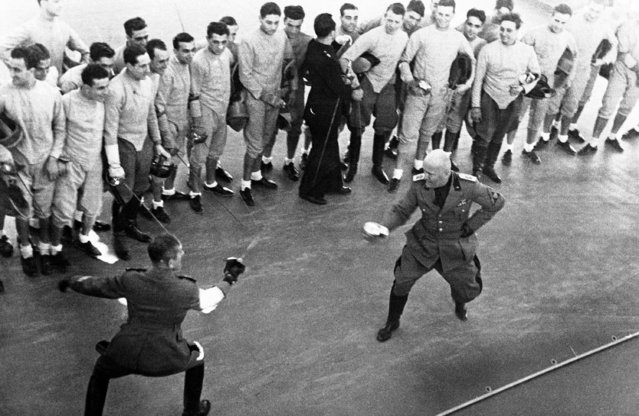 Benito Mussolini, right, fighting a fencing duel with a Fascist militia officer in Rome, on November 23, 1936. The match is watched by Nazi newspapermen, who are visiting Rome, and Fascist officials. (Photo by AP Photo)