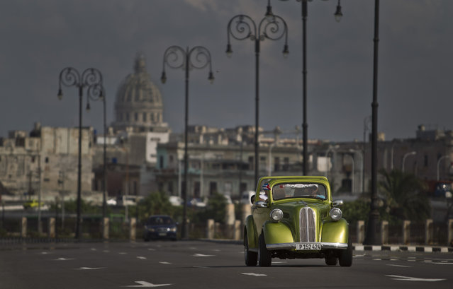In this October 15, 2014 photo, a man drives a classic American car on The Malecon in Havana, Cuba. This classic still running on the streets of Havana is part of a fleet of classic cars that have become an icon of tourism in the socialist nation. (Photo by Franklin Reyes/AP Photo)
