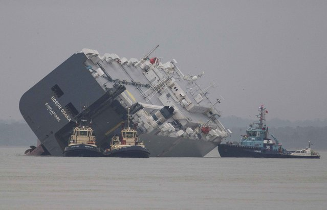 The cargo ship Hoegh Osaka lies on its side after being deliberately ran aground on the Bramble Bank in the Solent estuary, near Southampton in southern England January 5, 2015. The vessel was deliberately run aground on Saturday evening after it began to list, according to its owners Hoegh Autoliners. (Photo by Peter Nicholls/Reuters)