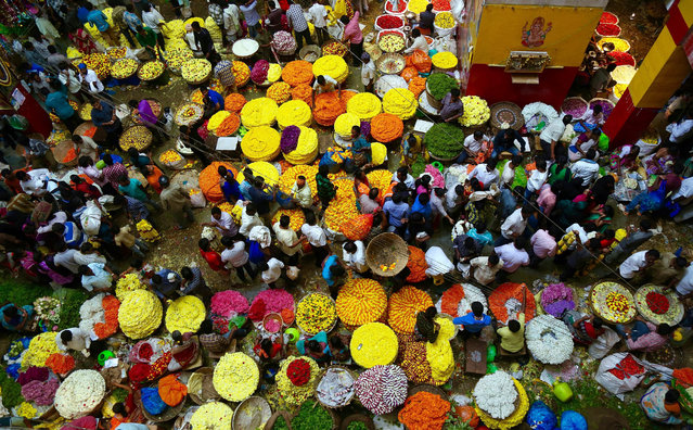 Visitors buy flowers at a flower market on the eve of Hindu goddess Durga Puja festival in Bangalore, India, 10 October 2016. The nine-day Hindu festival celebrates the killing of a demon king by the Goddess Durga representing the victory of good over evil and ends with colourful celebrations all over the country. Navratri festival runs from 03 to 11 October. (Photo by Jagadeesh N.V./EPA)