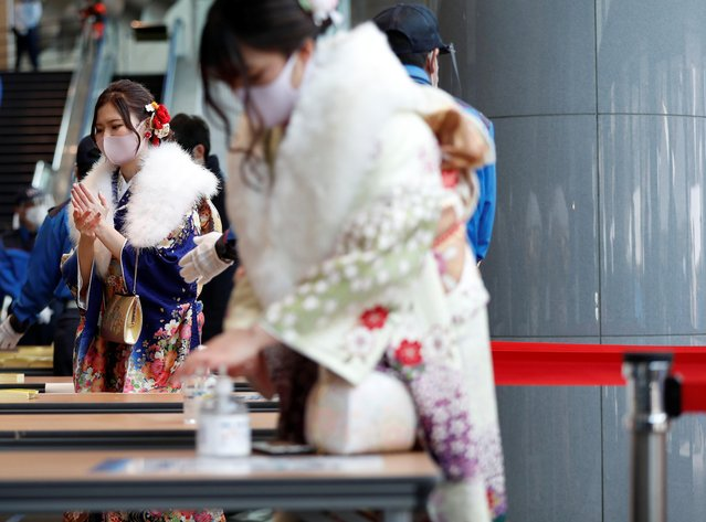 Kimono-clad youth wearing protective face masks disinfect their hands as they attend their Coming of Age Day celebration ceremony at Yokohama Arena during the government declared the second state of emergency for the capital and some prefectures, amid the coronavirus disease (COVID-19) outbreak, in Yokohama, south of Tokyo, Japan on January 11, 2021. (Photo by Issei Kato/Reuters)