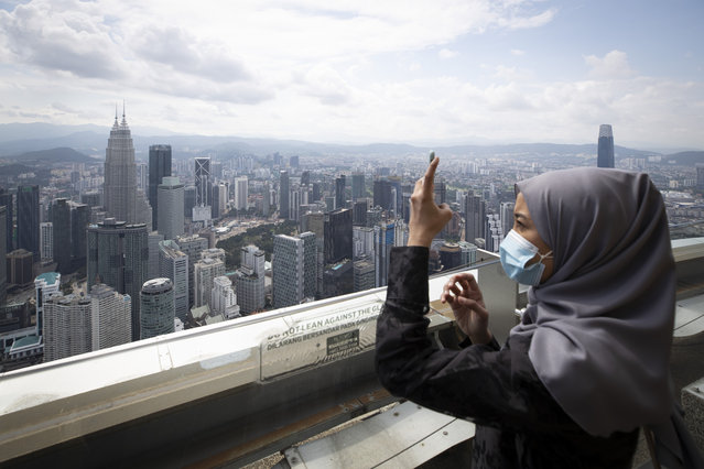 Tourist wearing a face mask takes picture at observation deck at Kuala Lumpur Tower in Kuala Lumpur, Malaysia, Wednesday, July 1, 2020. Malaysia entered the Recovery Movement Control Order (RMCO) after three months of coronavirus restrictions. (Photo by Vincent Thian/AP Photo)