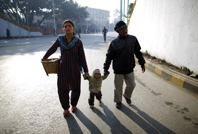 A family walks along the deserted road as they head towards work during the general strike independently called by the Unified Communist Party of Nepal (Maoist) and led by 30 party alliance and the Communist Party of Nepal (Maoist), demanding that the drafting of the new constitution is done on time through consensus, in Kathmandu January 13, 2015. (Photo by Navesh Chitrakar/Reuters)