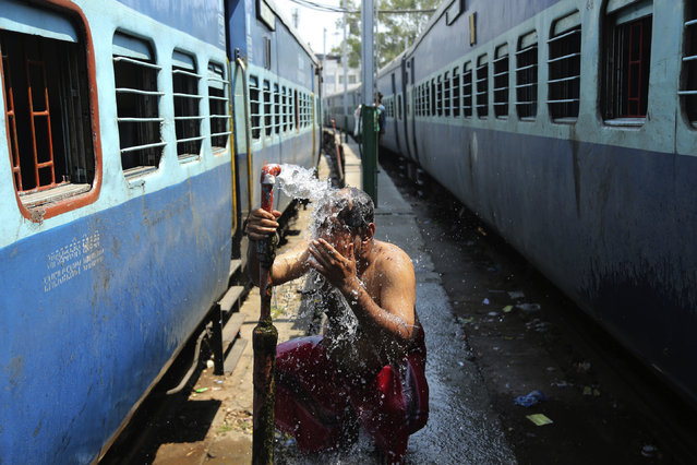 An Indian passenger bathes beside railway tracks on a hot summer afternoon in the outskirts of Jammu, India, Monday, May 28, 2018. The maximum temperature recorded in Jammu was 42.5 degrees Celsius, the highest this season which is a few degrees above normal for this time of the year. (Photo by Channi Anand/AP Photo)