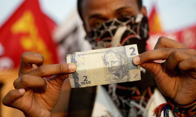 A demonstrator shows a 2.00 reais bill, the old transport fee of city buses, during a protest against fare hikes for city buses in Rio de Janeiro January 16, 2015. (Photo by Mauro Pimentel/Reuters)