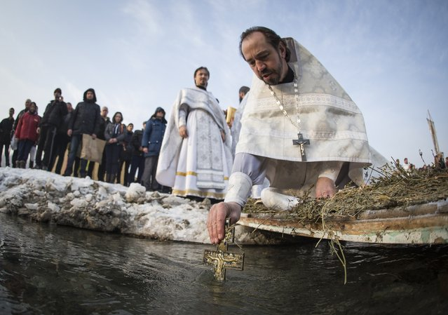 An Orthodox priest immerses a cross in the Bolshaya Almatinka river to bless its water during an Epiphany ceremony in Almaty, Kazakhstan January 19, 2015. (Photo by Shamil Zhumatov/Reuters)