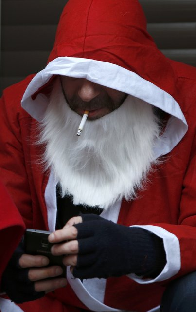 A man dressed as Santa Claus smokes as he takes part in the 22nd Santa Claus meeting in Auerbach, Germany, December 6, 2015. (Photo by Michaela Rehle/Reuters)