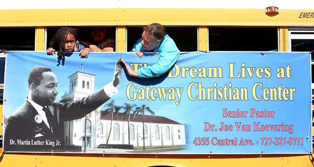 Diana Depaz, St. Petersburg touches the hand of Dr. Martin Luther King Jr., on a poster on the groups bus as it drives along Central Avenue, IN St. Petersburg, Fla., during the 30th annual MLK Drum Major for Justice Parade, Monday, January 19, 2015. (Photo by Scott Keeler/AP Photo/Tampa Bay Times)