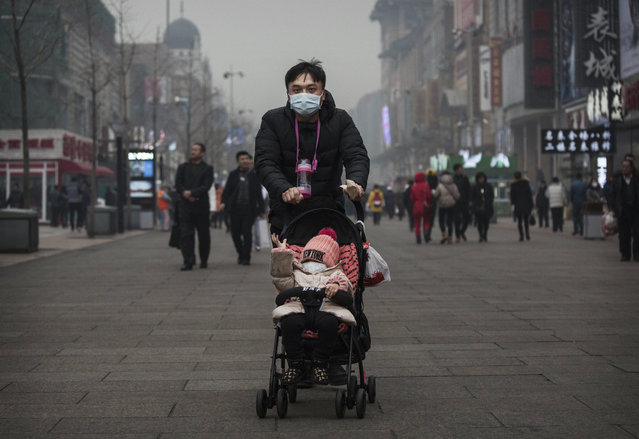"A Chinese man and his child wear masks to protest against pollution as they walk through a shopping area in heavy smog on December 8, 2015 in Beijing, China. The Beijing government issued a ""red alert"" for the first time since new standards were introduced earlier this year as the city and many parts of northern China were shrouded in heavy pollution. Levels of PM 2.5, considered the most hazardous, crossed 400 units in Beijing, lower than last week, but still nearly 20 times the acceptable standard set by the World Health Organization. (Photo by Kevin Frayer/Getty Images)"