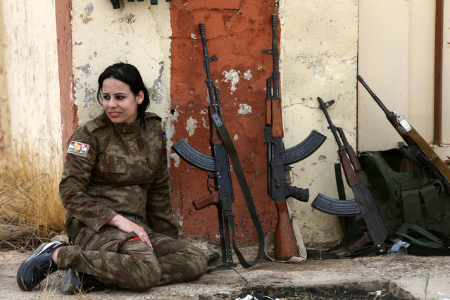 A Yazidi woman who joined the Kurdish Peshmerga forces sits next to rifles in the town of Bashiqa, after it was recaptured from the Islamic State, east of Mosul, Iraq November 10, 2016. (Photo by Alaa Al-Marjani/Reuters)
