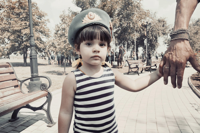 A little girl holds her father's hand during paratroopers' day in Donetsk. (Photo by Aude Osnowycz/The Guardian)