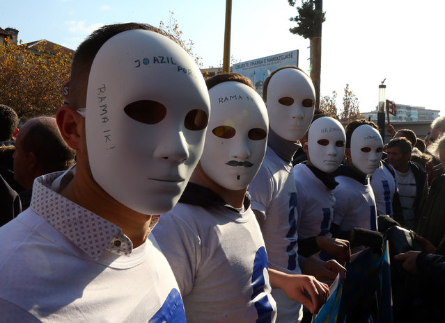 A group of Albanian opposition Democratic Party supporters wear masks during a rally in front of the Parliament building, in Tirana, Albania, Thursday, December 17, 2015, to protest against government's links to crime, corruption and taking the country into poverty. (Photo by Hektor Pustina/AP Photo)