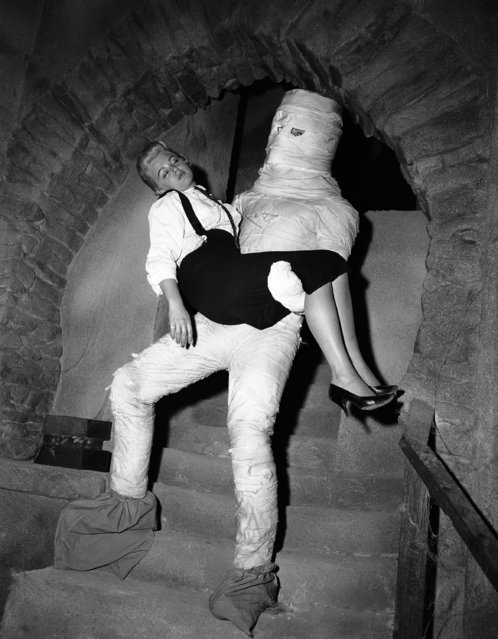 "Actor Mike Lane, standing six feet 10 inches in his stocking feet, makes a perfect monster as he carries actress Nancy Knox down the stairs into Frankenstein's dungeon, February 28, 1958. They have featured parts in the upcoming Boris Karloff movie ""Frankenstein 1970"". (Photo by David F. Smith/AP Photo)"