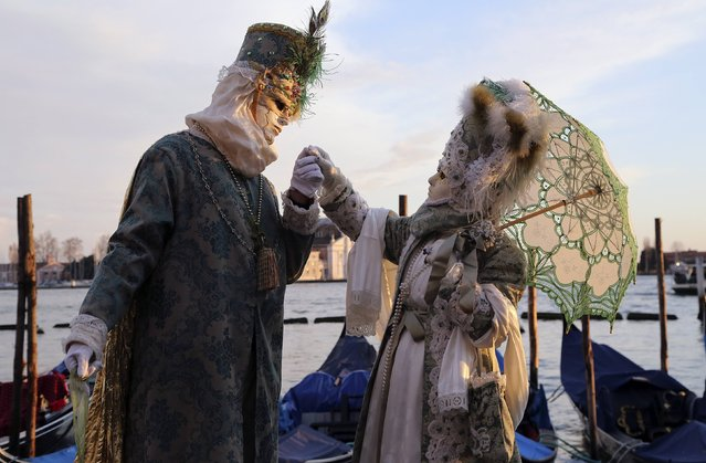 Masked revellers pose in front of St. Mark's square during the first day of carnival in Venice February 1, 2015. (Photo by Stefano Rellandini/Reuters)