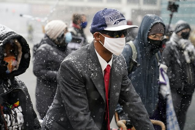 Protesters brave snowfall as they march around the Hennepin County Government Center, Monday, March 15, 2021, in Minneapolis where the second week of jury selection continues in the trial for former Minneapolis police officer Derek Chauvin. Chauvin is charged with murder in the death of George Floyd during an arrest last may in Minneapolis. (Photo by Jim Mone/AP Photo)