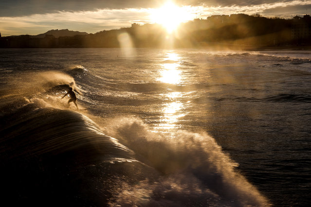 A surfer is seen off Ondarreta Beach at dawn in San Sebastian, Basque Country, northern Spain, 02 February 2021. The temperature reached up to 18 degrees Celsius during the day in the city. (Photo by Javier Etxezarreta/EPA/EFE)