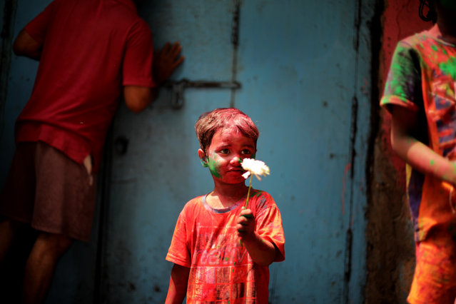 A child covered in color dust stands as tourists and locals celebrate Holi festival in Kolkata, Eastern India, 28 March 2021. The tradition of Holi, also known as Festival of Colors, heralds the beginning of spring and will be celebrated on 28 March in Bengal. (Photo by Piyal Adhikary/EPA/EFE)