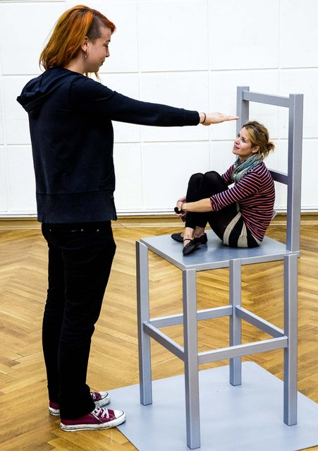 """Two women pose on a perspective chair in a temporary exhibition called """"Expedition of the Senses""""  in Berlin, Germany, on August 13, 2013. The Beuchet chair, named after French psychologist Jean Beuchet, baffles by the fact that two separate parts are seen as belonging together from a certain angle. (Photo by Gero Breloer/Associated Press)"""