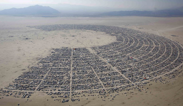 An aerial view of the Burning Man 2013 arts and music festival is seen in the Black Rock Desert of Nevada, August 29, 2013. The federal government issued a permit for 68,000 people from all over the world to gather at the sold out festival, which is celebrating its 27th year, to spend a week in the remote desert cut off from much of the outside world to experience art, music and the unique community that develops. (Photo by Jim Urquhart/Reuters)