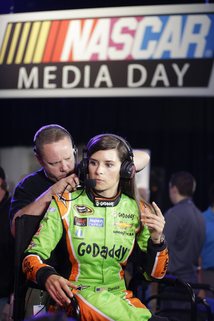 A technician adjusts the headset for driver Danica Patrick as she prepares for an interview during NASCAR media day at Daytona International Speedway, Thursday, February 12, 2015, in Daytona Beach, Fla. (Photo by John Raoux/AP Photo)