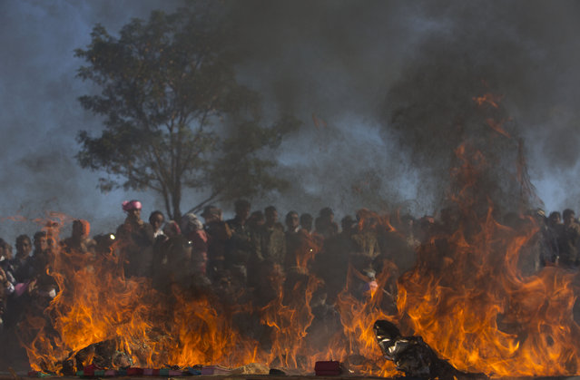 In this January 12, 2015 photo, Ta'ang people watch as opium, heroine and methamphetamine pills allegedly confiscated from pro-government militia are set on fire during a ceremony in Mar Wong Village, northern Shan state, Myanmar. (Photo by Gemunu Amarasinghe/AP Photo)