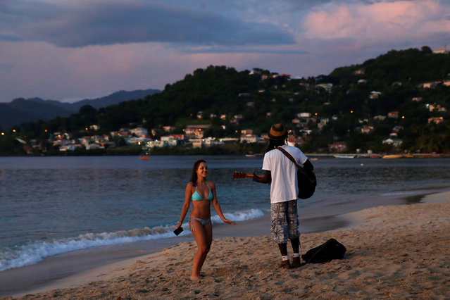 A woman is serenaded by a man playing the guitar and singing Bob Marley music at Grand Anse Beach during sunset in St. George's, Grenada, November 27, 2016. (Photo by Carlo Allegri/Reuters)