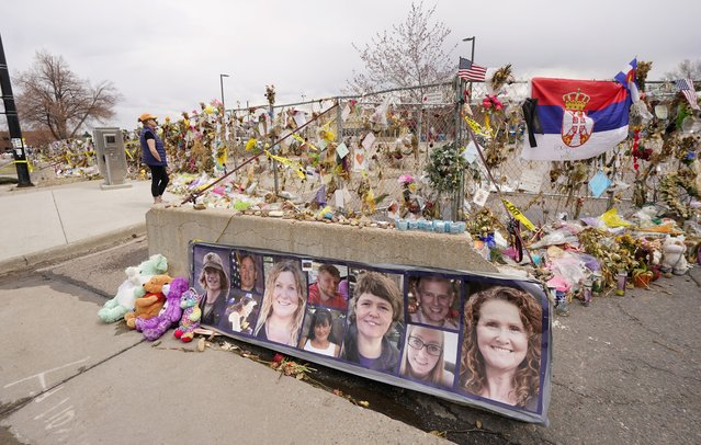 The photographs of the 10 victims of a mass shooting in a King Soopers grocery store adorn a cement barrier outside the store on Friday, April 23, 2021, in Boulder, Colo. The man accused of killing the people at the crowded Colorado supermarket last month armed himself with 10 high-capacity ammunition magazines, devices banned in the state after previous mass shootings, a prosecutor said Thursday. (Photo by David Zalubowski/AP Photo)